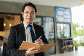 Asian Businessman Holding A Book And Pen To Write A Business Plan. He Standing And Looking Forward,  poster