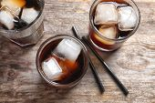 Glasses of refreshing cola with ice on wooden table poster
