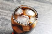 Glass of refreshing cola with ice on table poster