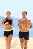 Fit athletes couple training running on beach sweating under the sun. Active fitness runners in spor poster