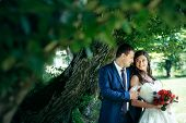 Horizontal Sensitive Portrait Of The Newlyweds Smiling, Tenderly Hugging And Looking At Each Other U poster