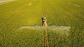 Aerial View Tractor Spraying The Chemicals On The Large Green Field. Spraying The Herbicides On The  poster