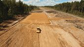 Construction Of A New Road In The Forest Area. Aerial View Construction Road Place. Construction Mac poster