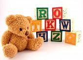 stock photo of teddy-bear  - a teddy bear and a stack of wooden alphabet blocks - JPG