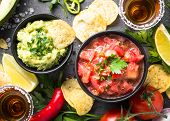 Latinamerican Mexican Food Party Sauce Guacamole, Salsa, Chips And Tequila On Black Table. Top View. poster