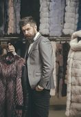 Man With Beard And Mustache Hold Fur Coat. Macho With Stylish Appearance Try White Sable Fur Coat. G poster