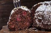 Chocolate Cake With Sour Cherries And Wallnuts Cut Into Several Pieces On The Wooden Rustic Backgrou poster