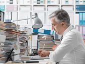 Businessman Working In The Office And Piles Of Paperwork poster