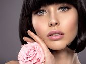 Woman with beauty short black hair holding rose flower. Fashion model with  straight hair. Fashion m poster