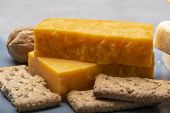 Cheese Collection, Matured And Orange Original British Cheddar Cheese In Blocks Served On Grey Plate poster