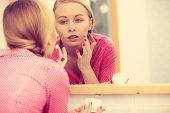 Young Blonde Woman Applying Moisturizing Skin Cream On Face, Looking In Bathroom Mirror. Girl Taking poster