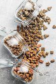 Dry pet food. Kibble dog or cat food in jar. Top view. poster