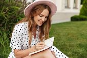 Image of amazing happy cheerful young redhead woman sit on green grass outdoors writing notes in not poster