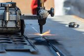 Motswana welder worker in a Botswana workshop, using an acetylene torch to cut in straight line, rol poster