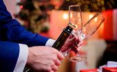 Toast And Cheers Concept. Male Hands Opening Champagne Bottle On Christmas Decorations Background. L poster