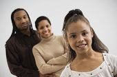stock photo of nuclear family  - Studio shot of African girl smiling with parents in background - JPG