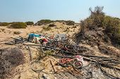 Pile Of Old Rusty Discarded Bicycles Laying On Sand In Strong Sun. All Brands / Logos Removed. poster