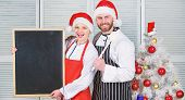 Man And Woman Chef Santa Hat Near Christmas Tree Hold Blackboard Copy Space. Couple Check List Ingre poster