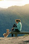 Woman Hiker Sitting On Bench And Playing With Small Dog On Top Of The Hill. Hiking, Pets, Animal Fri poster