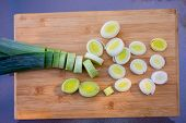 Organic Fresh Cutted Leeks On The Wooden Cutting Board. Leek Cut By Means Rings On A Chopping Board. poster