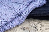 Knitted Wool Sweaters. Pile Of Knitted Winter Clothes On Wooden Background, Sweaters, Knitwear, Spac poster