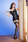 stock photo of tease  - Humorous image of teasing fifties pinup model in black satin lingerie and stockings - JPG