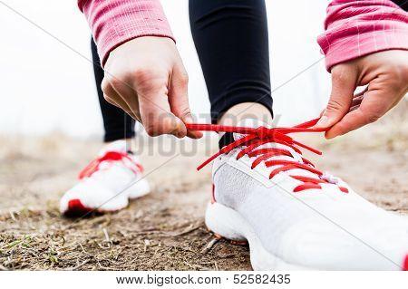 Постер, плакат: Женщина бегун связывая спортивная обувь, холст на подрамнике