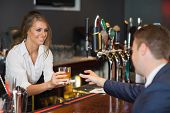 picture of tumbler  - Beautiful waitress serving handsome businessman in a classy bar - JPG