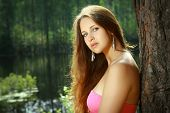stock photo of 16 year old  - Beautiful Girl 16 years old with long brown hair and a pink dress stands alone on a green background of the forest and water on a summer day in the sun.