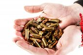 stock photo of 9mm  - a heap of 9mm pistol bullets holded by human hands isolated over a white backgrounds - JPG