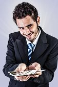 stock photo of cheater  - an elegant young businessman holding a deck of playing cards - JPG