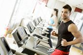 stock photo of treadmill  - Young man running on a treadmill at the gym - JPG