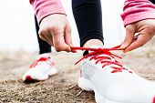 stock photo of legs feet  - Woman runner tying sport shoes - JPG