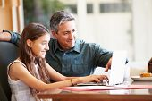 stock photo of 13 year old  - Father And Teenage Daughter Looking At Laptop Together - JPG