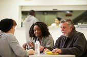 pic of homeless  - People Sitting At Table Eating Food In Homeless Shelter - JPG