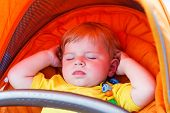 Lovely Toddler Boy Sleeping Outdoor In Orange Stroller.