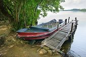 stock photo of dock a pond  - motorboat at the dock on the river bank                                     - JPG