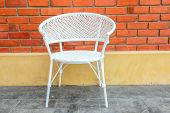 white chair with red brick wall