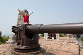 Boy on a gun in the old Russian fort in Lyushyun (Russian name Port Arthur). East China.