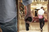 stock photo of gangster  - Man Holding Gun against an hotel background - JPG