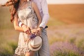 stock photo of lavender field  - Young beautiful sensual couple kissing outdoors in windy weather in the summer on a lavender field - JPG