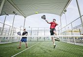 picture of paddling  - Two men playing paddle tennis in wide angle shot image - JPG