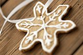 image of ginger bread  - White Decorated Ginger Bread Star Cookie on white Ribbon as Macro as Background on Wood