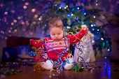 foto of christmas baby  - Cute funny baby girl sitting uder Christmas tree - JPG