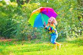 stock photo of rainy weather  - Funny cute curly toddler girl wearing yellow raincoat and boots holding colorful umbrella playing in the garden by rain and sun weather on a warm autumn or summer day