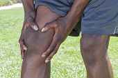 picture of knee  - Closeup of knee and leg of lean African American male athlete clutching injured knee with fingers around the patella on green lawn outdoors - JPG