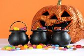 stock photo of happy halloween  - Happy Halloween candy in trick or treat carry cauldrons with pumpkin on orange background - JPG