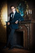 foto of handsome  - Young handsome man in elegant suit stands by the fireplace in a room with classic vintage style - JPG