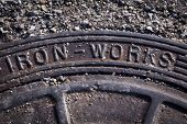 picture of manhole  - Close up of a metal manhole cover with the words Iron Works - JPG