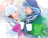 foto of hot couple  - Happy Winter Couple drinking hot beverage outdoors - JPG